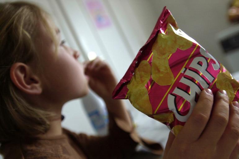 Une petite fille mange des chips, le 30 octobre 2003 à Caen (Illustration)