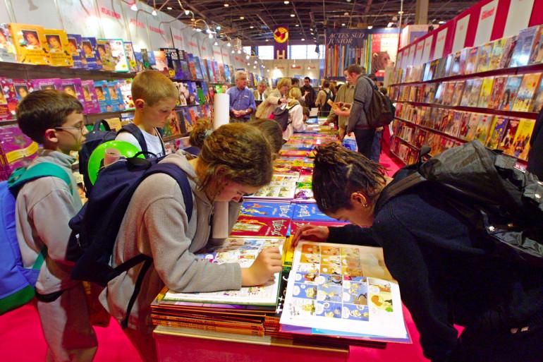 Des enfants lisent dans le rayon bande dessinée du Salon du livre, le 16 mars 2001 à Paris