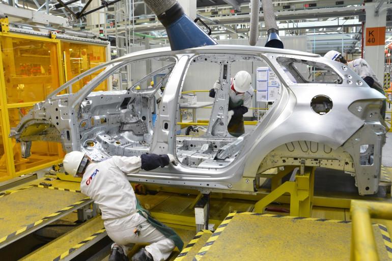 Des ouvriers assemblent un véhicule Peugeot dans une usine de PSA