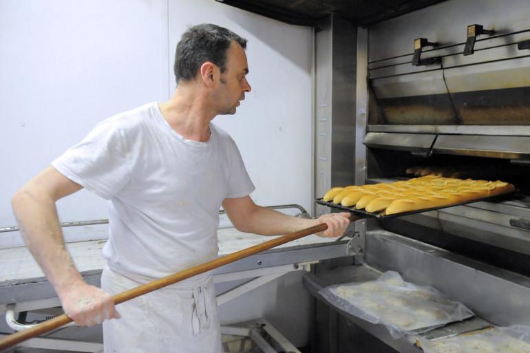 Un boulanger sort son pain du four (illustration)