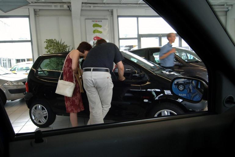 Un couple regarde l'intérieur d'une automobile, le 1er août 2005, chez un concessionnaire Renault à Hérouville