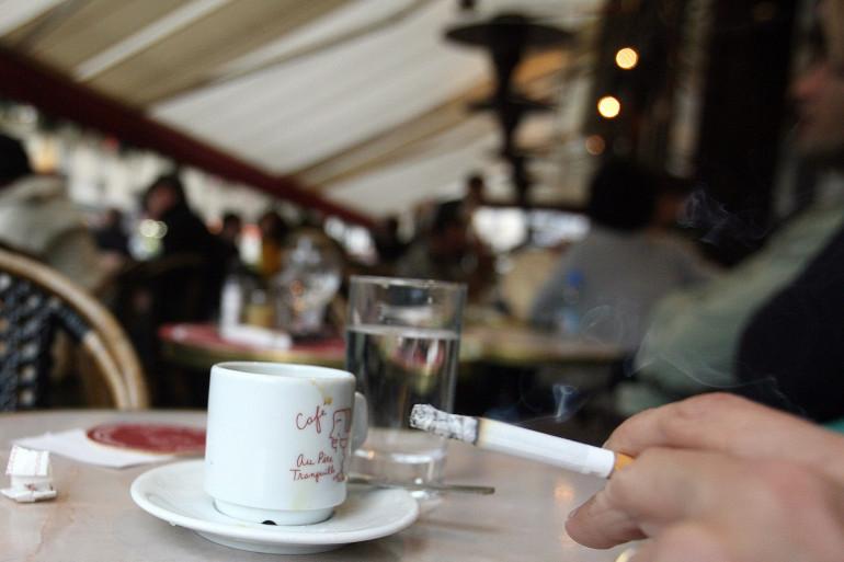 Un fumeur prenant un café, assis à une terrasse chauffée (illustration)