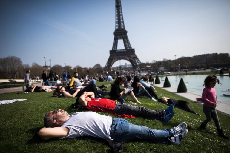 Des personnes profitent du soleil près de la tour Eiffel à Paris, le 26 mars 2017