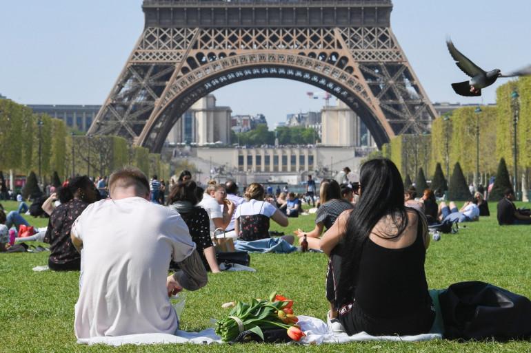 Des personnes profitent du soleil près de la tour Eiffel, le 18 avril 2018