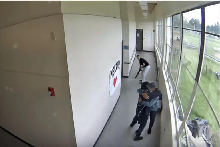 Le surveillant prenant des ses bras l'élève qu'il vient de désarmer