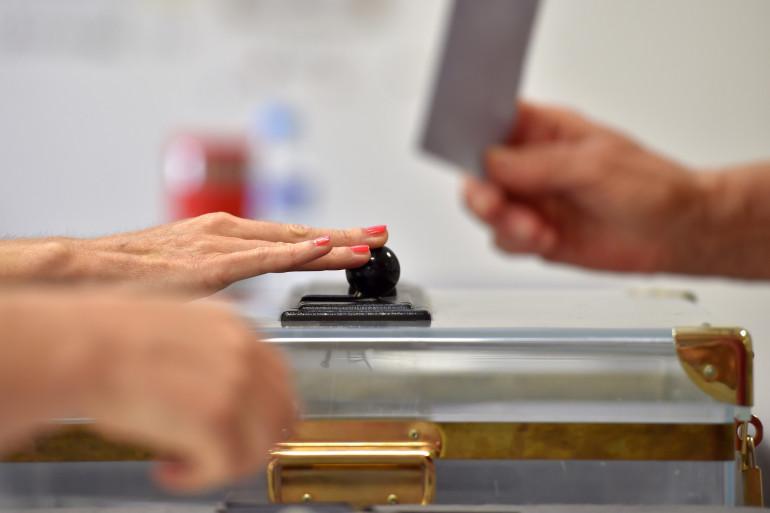 Une personne glisse un bulletin dans une urne lors d'une élection (illustration)