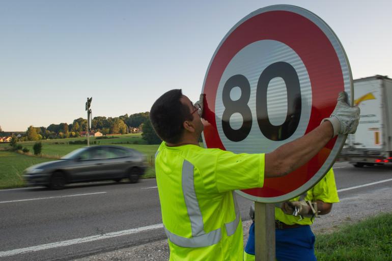 Un employé de la DIR Est installe un nouveau panneau de signalisation sur la nationale 57.