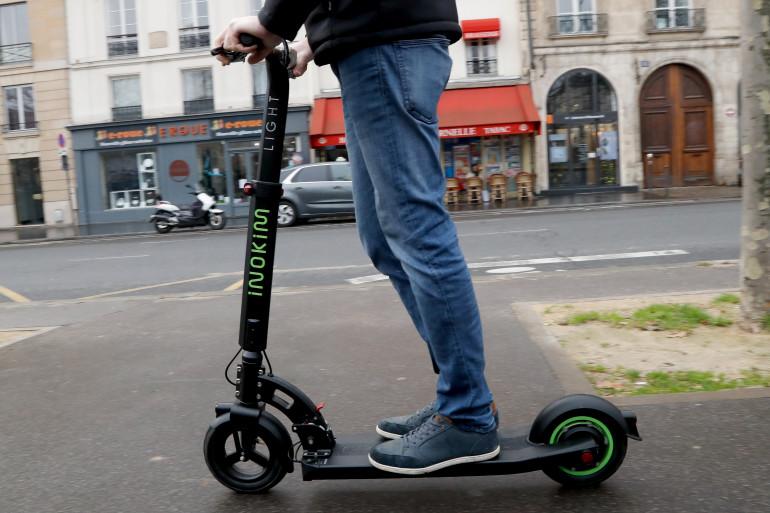 Un homme fait de la trottinette électrique à Paris.