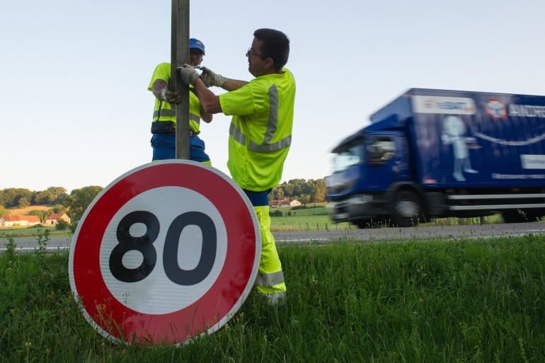 Des agents de la DDE installent un panneau de limitation à 80 km/h sur la RN57, à Hyet
