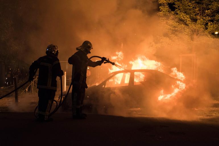 Des pompiers éteignent une voiture en flammes à Nantes, dans la nuit du 3 au 4 juillet 2018