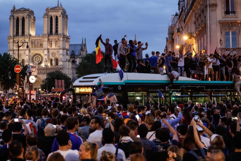 Près de Notre-Dame de Paris, des supporters français sont montés sur un bus RATP pour célébrer leur joie après la qualification de la France en finale de la Coupe du Monde.