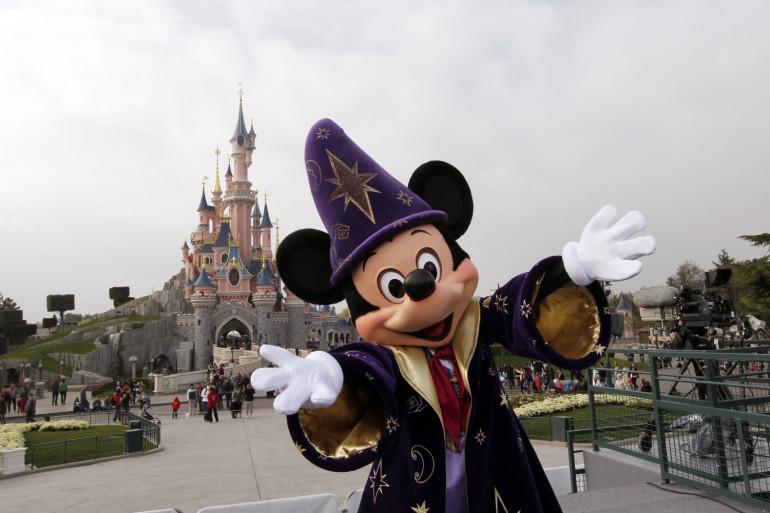 Mickey posant devant le château de la Belle au bois dormant, au parc Disneyland Paris (illustration).