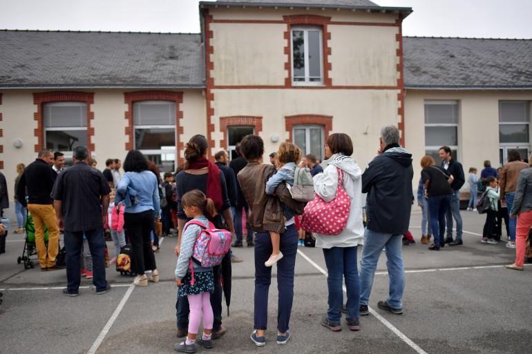 Des parents d'élèves et leurs enfants attendent devant l'école le jour de la rentrée des classes à Vertou en 2017.