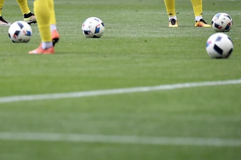 Crampons et ballons sur un terrain de football (illustration)