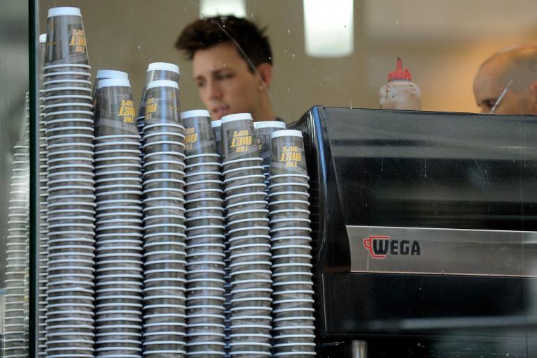 Des gobelets devant une machine à café (Ilustration)