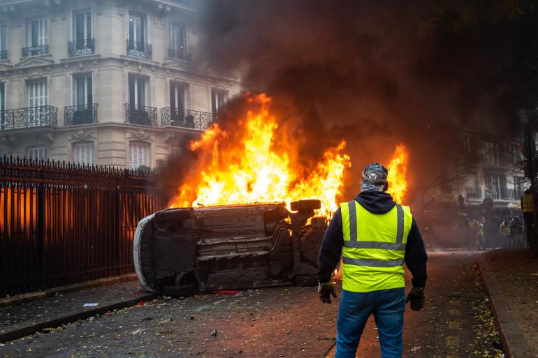 Un gilet jaune devant un voiture en train de brûler avenue Foch, non loin de l'Arc de Triomphe à Paris.
