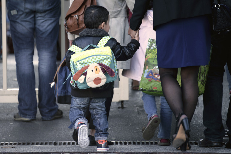 Un petit garçon sur le chemin de son école maternelle.