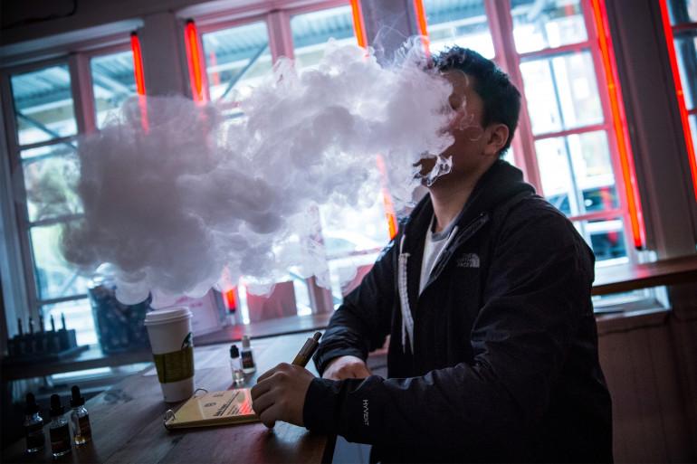 Un jeune homme fumant une cigarette électronique (illustration)