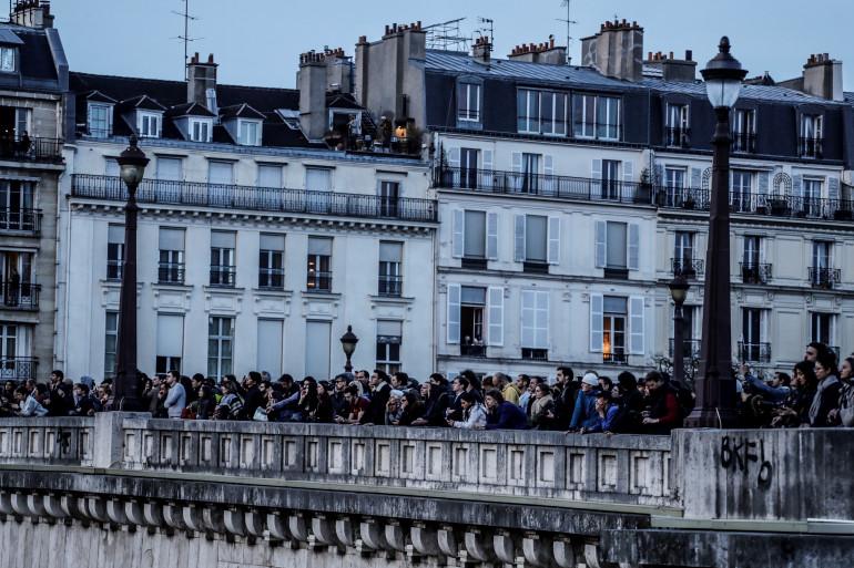 Des centaines de passants ont pris place sur les bords de la Seine pour observer l'incendie qui ravage Notre-Dame de Paris.