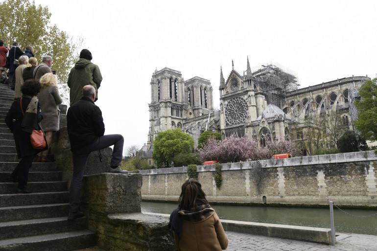 Des riverains contemplent Notre-Dame de Paris incendiée la veille, le 15 avril 2019