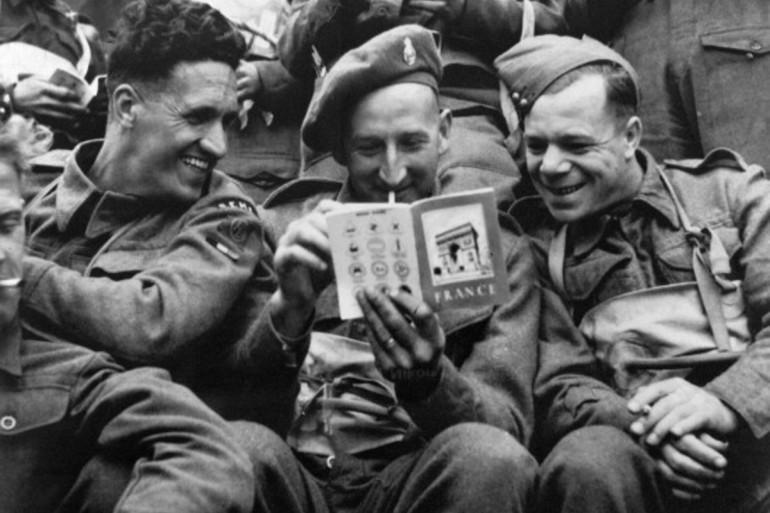 Des soldats britanniques lisent un guide touristique sur la France dans une barge de débarquement