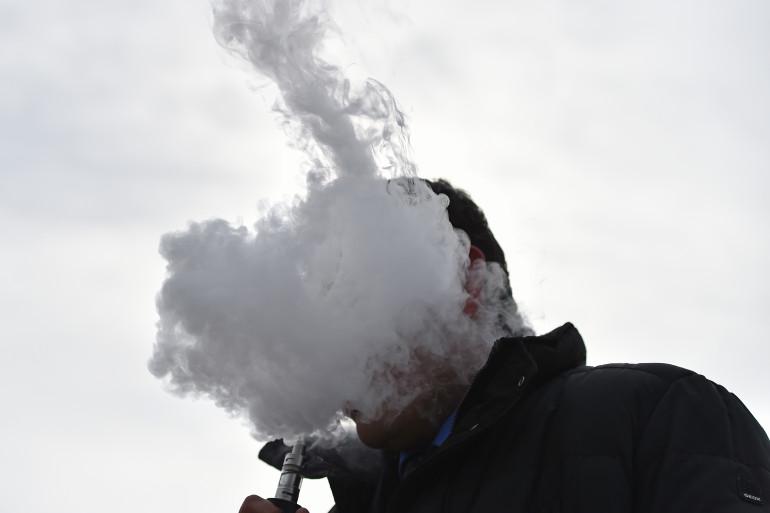 Un homme vapote une cigarette électronique