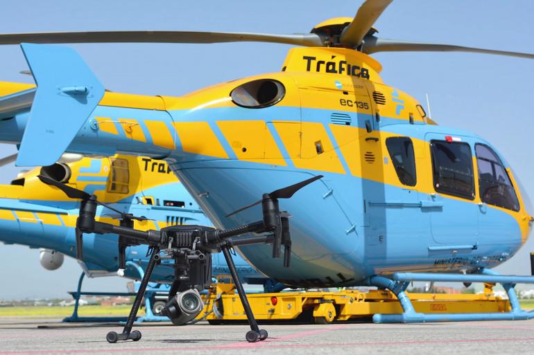 Un drone équipé d'une caméra haute résolution, photographié devant un hélicoptère du Département national espagnol du trafic (DGT)