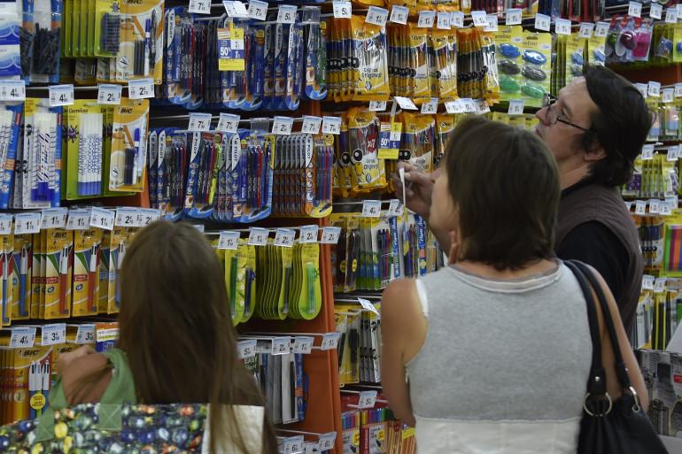 Une famille au rayon des fournitures scolaires dans un supermarché (illustration).