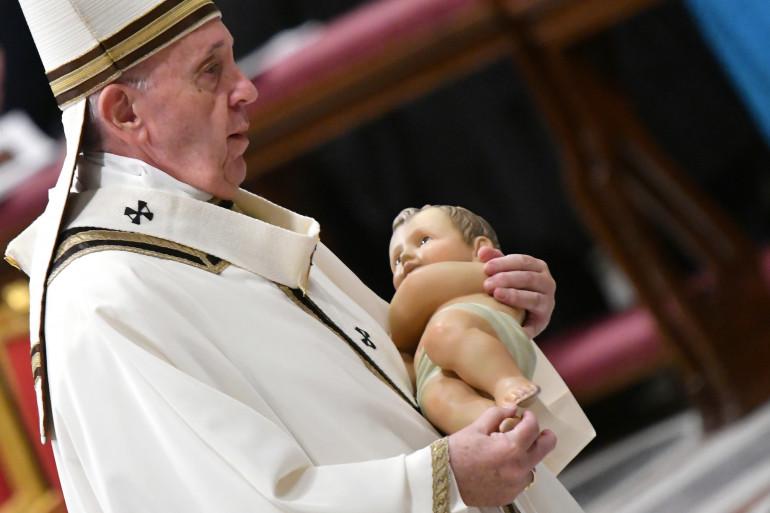 Le 24 décembre 2019, le Pape François porte une statue représentant l'enfant Jésus pour la place dans la crèche lors de la messe de minuit