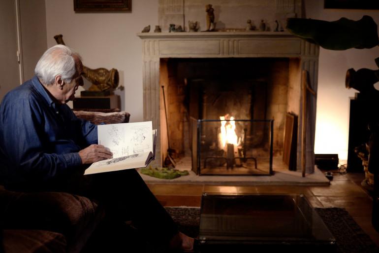 Un homme lit un livre devant un feu de cheminée en 2014 à Paris (illustration)