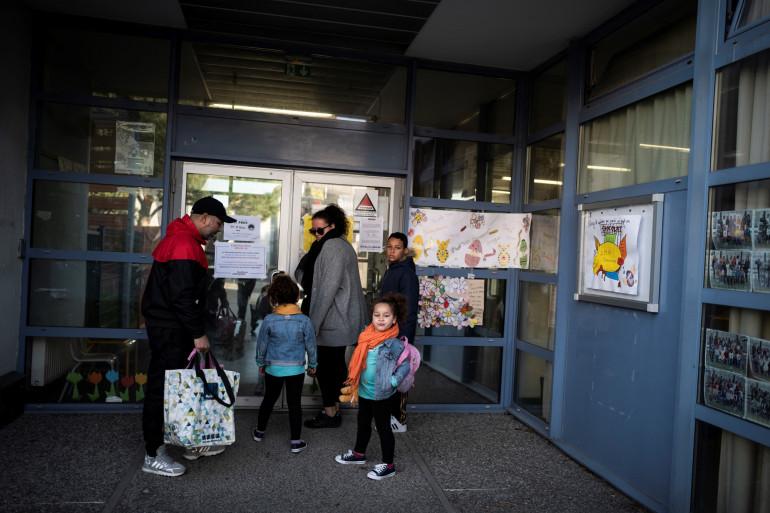 Des parents et leurs enfants devant une garderie (illustration).