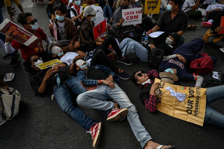 Des manifestants se sont couchés pour bloquer une route lors d'une manifestation contre le coup d'État militaire à Yangon le 20 février 2021.