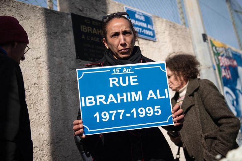 Une femme tenant une pancarte de rue au nom d'Ibrahim Ali lors d'une commémoration à Marseille, le 21 février 2020, alors que les proches de la victime demandait une inauguration officielle de l'avenue.