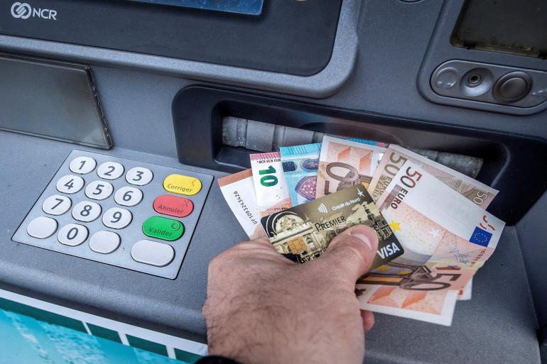 Un homme retire de l'argent d'un distributeur automatique de billets à Lille, dans le nord de la France, le 4 janvier 2017.
