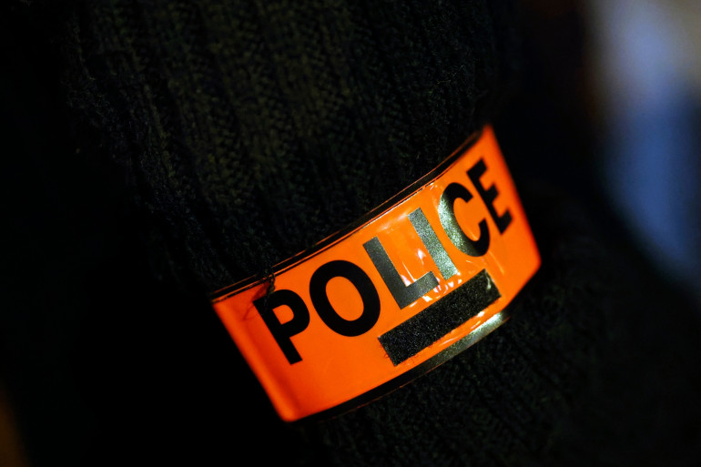 Cette photo prise à Créteil, dans la banlieue sud-est de Paris, le 8 décembre 2020, montre un brassard de police alors que des policiers se tiennent devant la «Direction territoriale de la titrisation du Val-de-Marne».