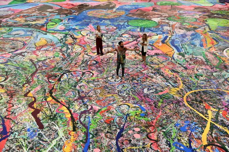 """L'artiste Sacha Jafri au milieu de son tableau """"Journey of Humanity"""", le plus grand du monde"""