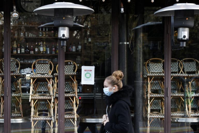 Une femme portant un masque, devant un restaurant fermé à paris, le 18 novembre 2020.