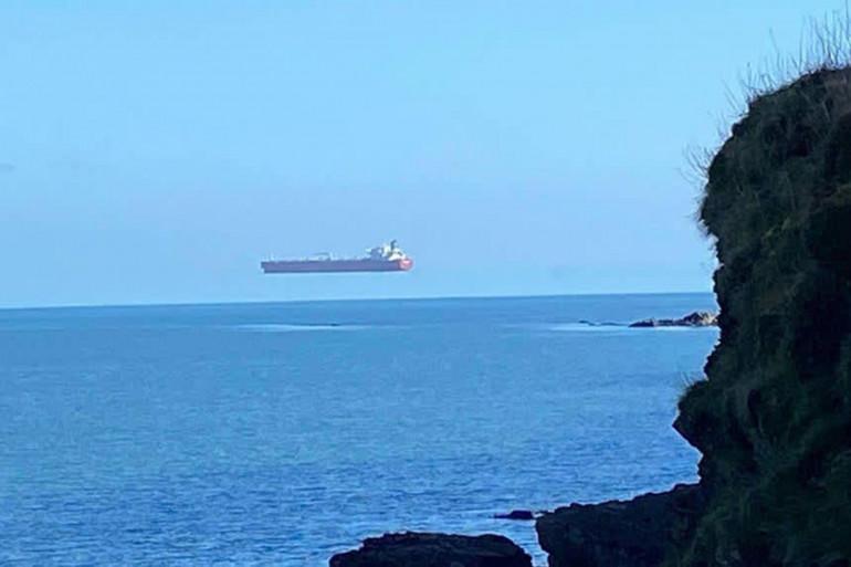 La photo, prise par le photographe David Morris, montre un bateau semblant flotter au dessus de l'eau. Il s'agit en réalité d'une illusion d'optique très rare.