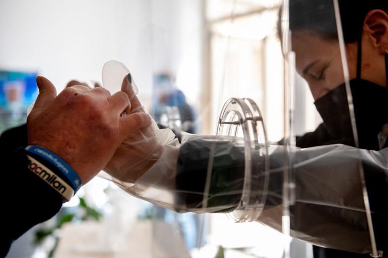 Un résident dans une maison de retraite tient la main d'un proche à Rome le 3 mars 2021