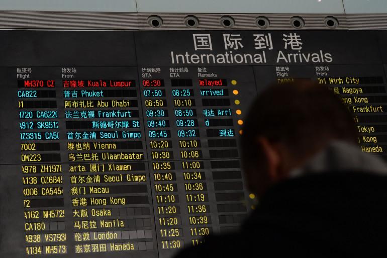 Un homme devant le tableau de vols indiquant un problème dans l'arrivée de l'avion MH370 de la Malaysia Airlines