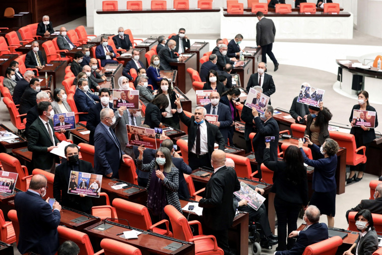 Le député turc du Parti démocratique populaire de gauche Omer Faruk Gergerlioglu réagit alors qu'il est entouré de députés, après avoir été démis de ses droits à la suite d'un vote au Parlement turc à Ankara, le 17 mars 2021.