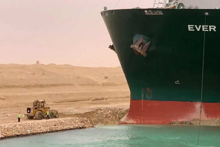 Une pelleteuse tente de déblayer les sable sous le porte-conteneur de 400 mètres de long