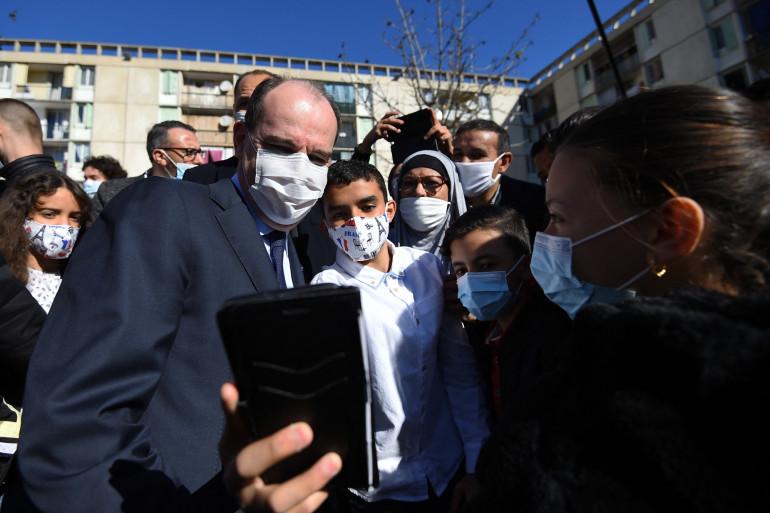 Le Premier ministre Jean Castex pose avec des habitants alors qu'il visite le quartier de Pissevin à Nîmes, le 27 mars 2021.