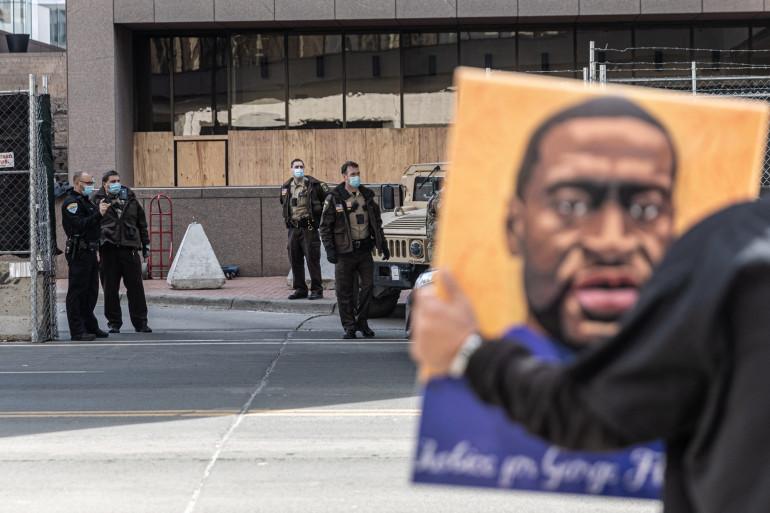 Un manifestant brandit un portrait de George Floyd devant le tribunal de Minneapolis