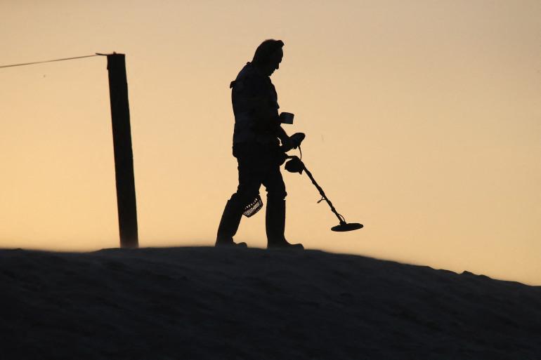 Un homme cherchant des trésors sur la plage avec un détecteur de métaux