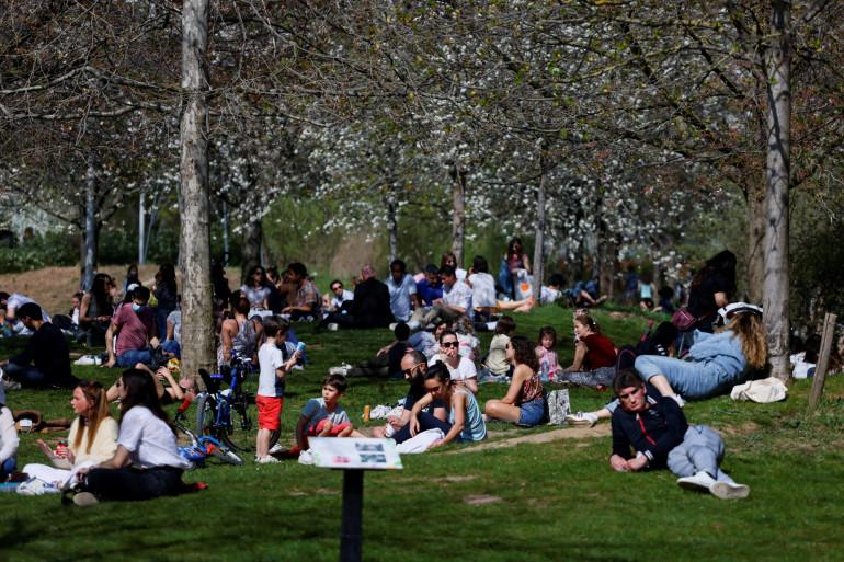 Le 31 mars 2021, les gens sont assis dans l'herbe du parc Clichy-Batignolles-Martin Luther King, dans le 17ème arrondissement de Paris.