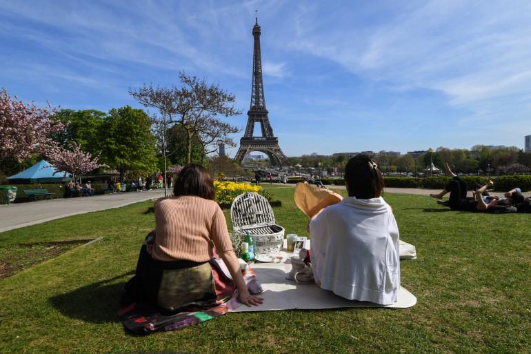 Deux personnes faisant un pique-nique face à la Tour Eiffel à Paris.