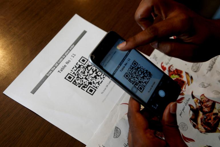 Une personne scanne un QR code dans un restaurant (illustration)