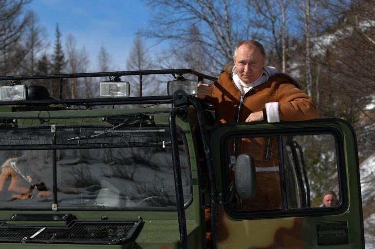 Vladimir Poutine, posant sur un véhicule militaire, en Sibérie, le 21 mars 2021