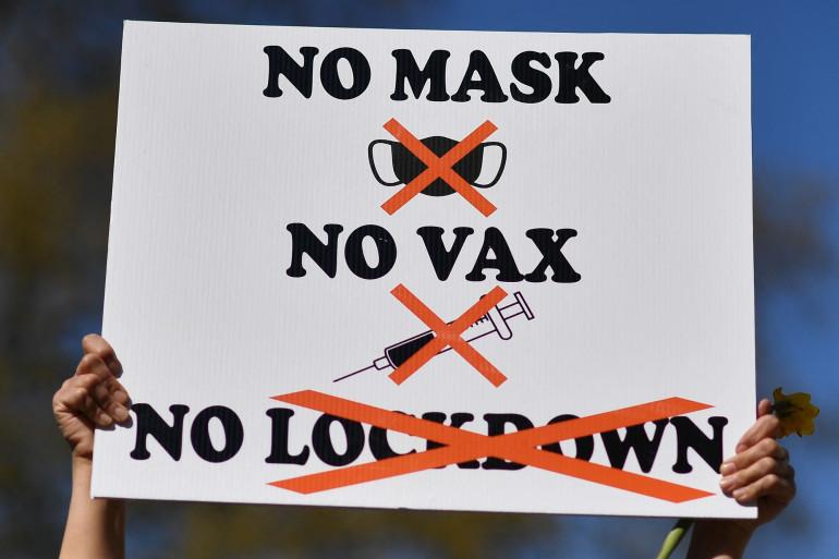 Une manifestante tient une pancarte anti-vaccin et anti-confinement.